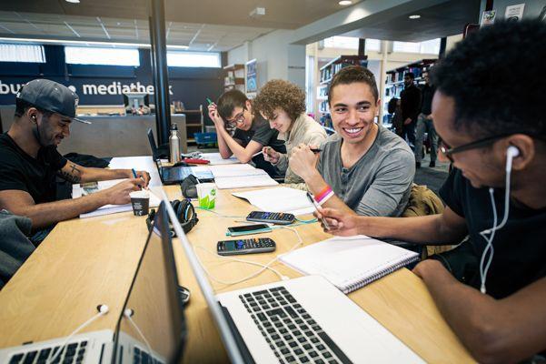 Studenten des Studiengangs Civil Engineering sitzen zusammen am Tisch und lernen an ihren Laptops