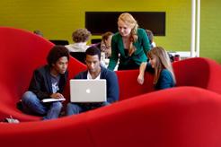 Studenten der Vrije Universiteit Amsterdam auf rotem Sofa mit Laptop